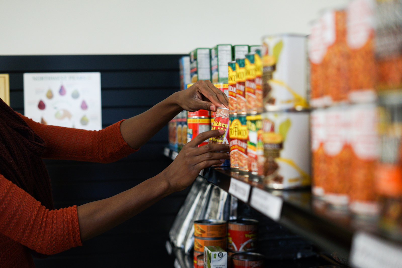 A person is restocking shelves with cans of food