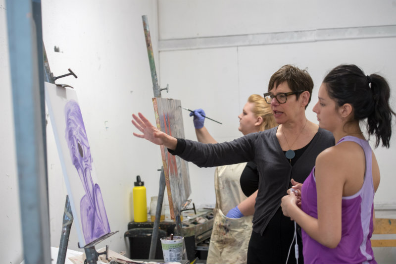 an instructor directs a student as she's painting something purple on a canvas