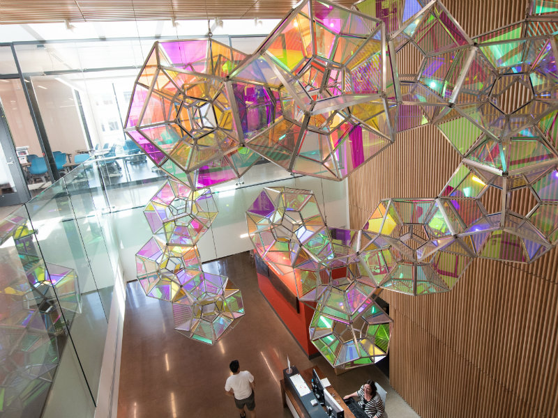 colorful glass artwork hangs in a stairwell