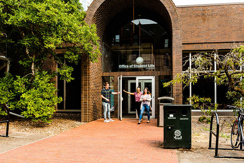 Students walk into the Office of Student Life, located in Snell Hall.