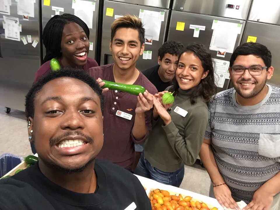 Students hold produce and mug for the camera in a cheesy way