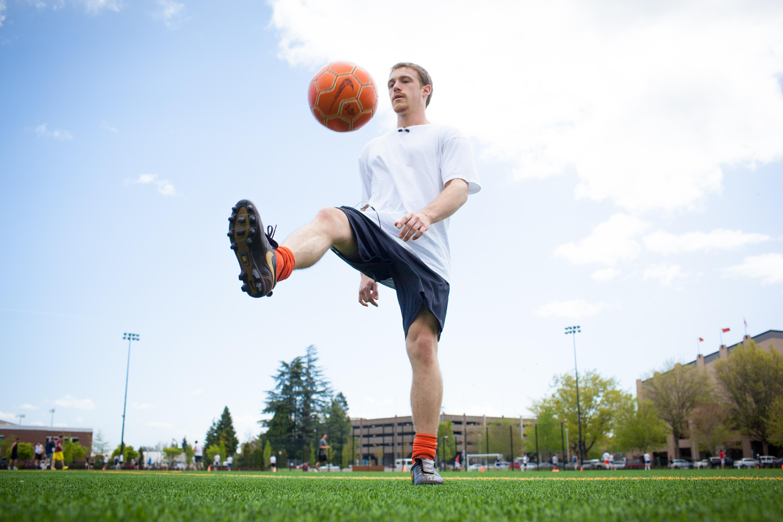 A student kicks a soccer ball around Student Legacy Park.
